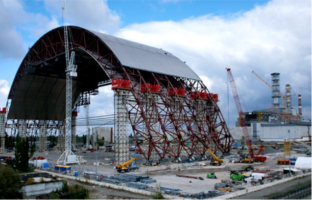 Caption: The Chernobyl New Safe Confinement (NSC) structure will ensure that the site of one of the worst nuclear disasters in history is stabilized and will pose no ongoing threat for future generations. The massive steel arch is 110m high, 165m long and a span of 260m. It is being constructed adjacent to the reactor so that it can be delicately pushed on Teflon pads to cover the temporary shelter that was built after the accident and entomb the radioactive remains of the reactor. Once in place the ends of the arch will be closed permanently to protect the environment from radiation releases and provide the infrastructure to support the deconstruction of the shelter and nuclear waste management operations.